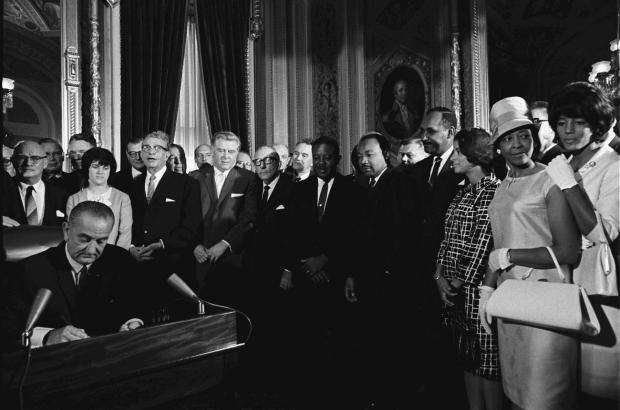 President Lyndon B. Johnson signs the Voting Rights Act of 1965 while Dr. Martin Luther King, Jr. and others look on.