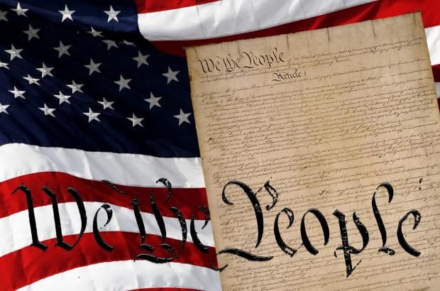 "Image of the U.S. flag and the U.S. Constitution with the words ""We the People"" in the forefront."