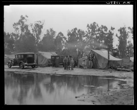 several people stand in front of fabric tents, a truck, scraggly trees, with a huge puddle in the foreground