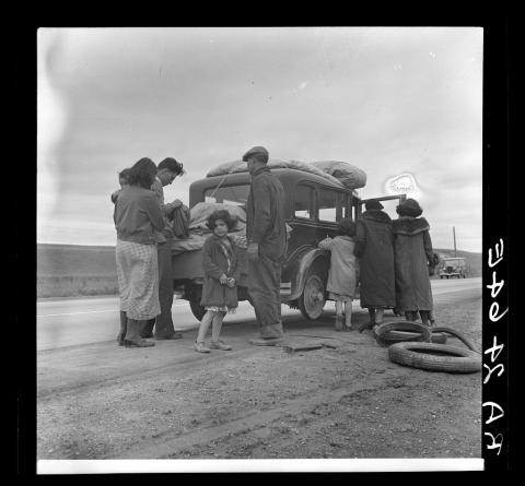 A family on the side of the road, gathered around a car and their luggage