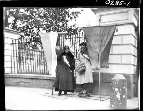 "Women hold banners at the White House gates on Jan 11, 1917, a day after their ""silent sentinel"" campaign for a woman's right to vote began."