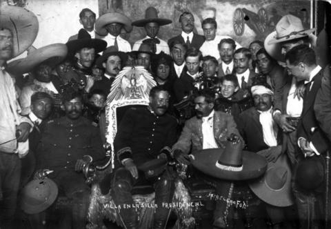 Francisco (Pancho) Villa, in the presidential chair, with Emiliano Zapata to his right. Mexico City, 1914.