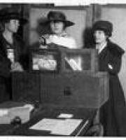 Three women in hats placing their votes at a ballot box