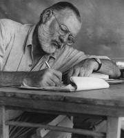 Ernest Hemingway Writing at his campsite in Kenya.