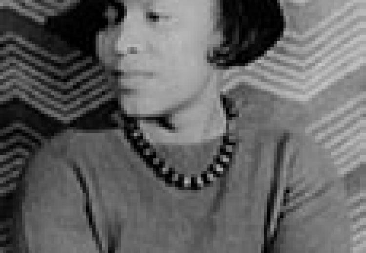 Zora Neale Hurston, in a black hat, grey sweater, and beaded necklace, face turned slightly to her left