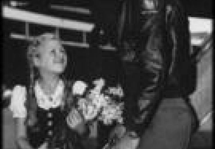 An american pilot looks down and smiles at a young girl wearing a dirndl, who hands the pilot a bunch of flowers