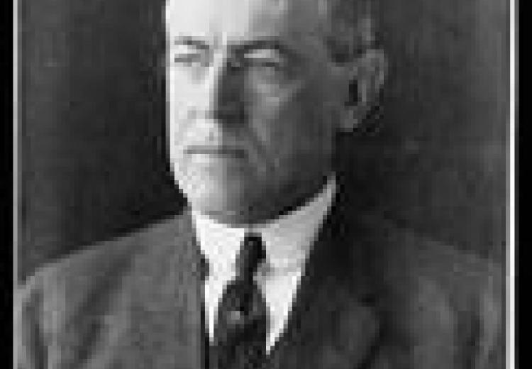 Woodrow wilson, black and white portrait, wearing a grey suit and black tie