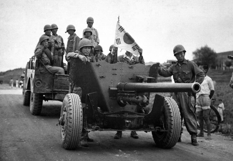 During South Korean evacuation of Suwon Airfield, a 37-mm anti-tank gun is hauled out of the area for repairs, by a weapons carrier. 1950