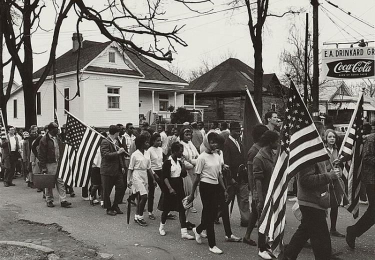 Participants, some carrying American flags, marching in the civil rights march from Selma to Montgomery, Alabama in 1965.