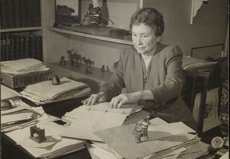 Photograph of Helen Keller seated at her desk and reading text in braille in Westport, Connecticut in 1950.