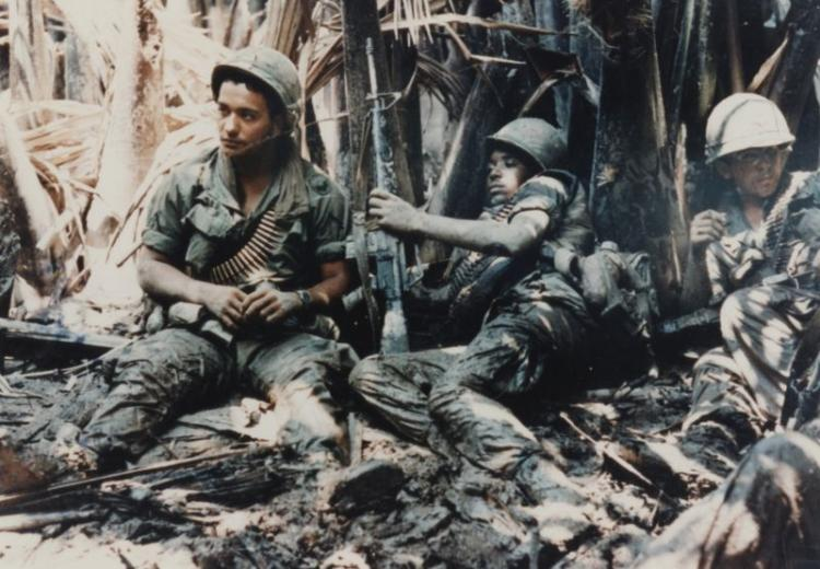 Privates First Class Carl Baden (New Orleans, Louisiana) and Arcadio Carrion (Puerto Rico) laying in the mud waiting for artillery to knock out the machine gun bunker that has them pinned down in a tree line at My Tho (April 4, 1968).