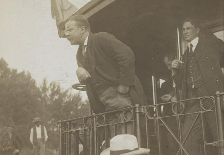 Teddy Roosevelt speaking at the back of a railroad car.