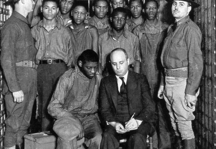 The Scottsboro Boys with their lawyer and guards